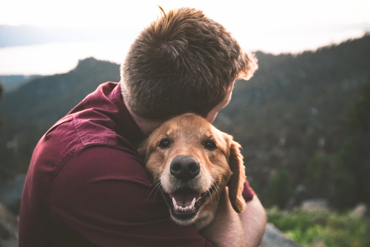 Homem e cachorro abraçados